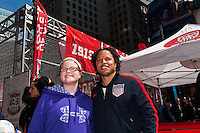 Former men's national team player Cobi Jones poses for a photo with a fan during the centennial celebration of U. S. Soccer at Times Square in New York, NY, on April 04, 2013.
