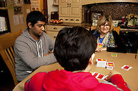 USA. Washington state. Fall City. ReStart Internet Addiction Recovery program at Heavensfield Retreat Center. Shlok (L), Rosanne Sherlock (R) and Paul (back) seat and play cards (apples to apples' game) on the living room's table. Rosanne Sherlock is the daytime resident superviser. Shlok is 22 years old and is a citizen from India. Paul is 19 and a british citizen from England. Both have dropped out of university because they were highly addictive online video gamers on internet. ReStart is an unique intensive onsite program which offers to participants an opportunity to stay in a retreat center designed to promote insight and renewal, disconnect from digital distractions, and engage in coaching and mentoring while building a blue print for change. The three to six-month reStart program, the first of this kind in the United States, works to help men over 18, suffering from problematic internet, video game, social media and technology use by teaching positive and sustainable lifestyle change in a serene, rural environment surrounded by nature. 11.12.2014 © 2014 Didier Ruef
