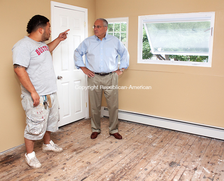 WATERBURY CT-JULY 18 2011 - 071912DA02-  Christopher Germosen, left, talks with Leo J. Frank Chief Executive Officer of Waterbury Development Corporation on Thursday during a tour of a transformed blighted house that Germosen bought a for $1,000 at a tax auction on Chestnut Ave. in Waterbury.Darlene Douty Republican-American