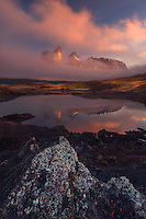 Los Cuernos del Paine peaks through low clouds illuminated by the rising sun on a foggy morning.