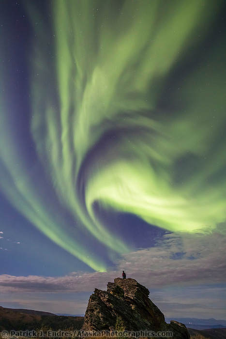 A man watches the aurora borealis, also called the northern lights, from a rock outcrop as they swirl over the foothills surrounding Fairbanks, Alaska.