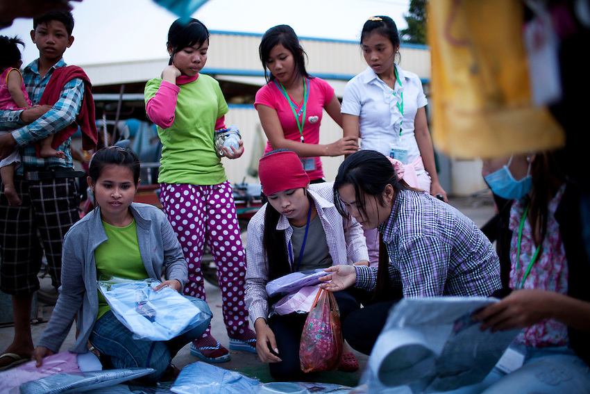 Workers from the Shen Zhou garment factory shop for clothes at a small open-air market just outside the factory in Phnom Penh, Cambodia, September 14, 2011. Clothes like pajamas, which are often worn outside the home in Cambodia, cost around US$2 to $2.50 per set.