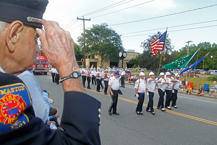 Thomaston, CT-080313MK10 Stephen Shypinka,  with 60 years of service in the Thomaston fire department and grand marshal of the annual Thomaston Firemen's Parade, salutes the American flag and members of the Sandy Hook fire department as they march past the reviewers stand Saturday evening in Thomaston. Michael Kabelka / Republican-American