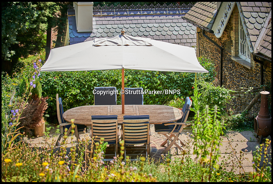 BNPS.co.uk (01202 558833)<br /> Pic: Strutt&Parker/BNPS<br /> <br /> Al-fresco dining...<br /> <br /> Good enough to eat!<br /> <br /> A fairytale-style home that looks like it could be made out of gingerbread has gone on the market for £1.25m.<br /> <br /> The quaint and quirky Firbank House was once the coachhouse and stables for a country mansion before it was turned into a home in the 1950s.<br /> <br /> The Grade II listed period property has a Victorian Gothic style, with lots of ornate decorative touches, including a cupola and a decorative slate roof with fleur-de-lys ridge cresting that look like something you'd see on a gingerbread house.<br /> <br /> The five-bedroom house in Tilford, Surrey, is now on the market with estate agents Strutt & Parker.