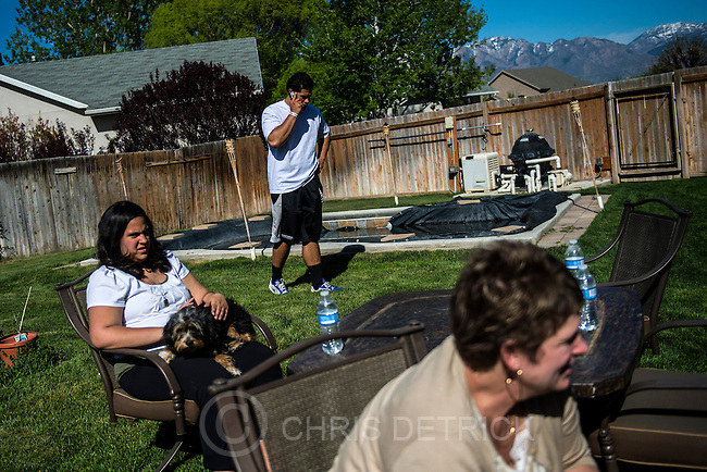 Chris Detrick  |  The Salt Lake Tribune<br /> Former Utah State tight end D.J. Tialavea talks with his agent while hanging out with his sister Abigail, mom Tami and dog Monkey at their home in West Jordan Friday May 2, 2014.