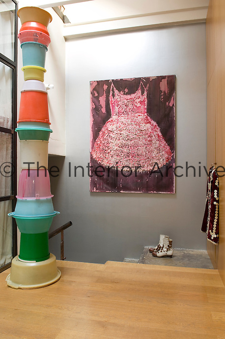 A tall column made out of plastic buckets, a large painting and a pair of boots form the focus of this landing