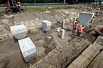 UTRECHT - Op knooppunt Oudenrijn plaatsen medewerkers van Heijmans Infrastructuur betonkoppen op de onlangs geslagen heipalen als onderdeel van een nieuw, experimenteeel wegdek, ModieSlab. Het door Heijmans Infrastructuur, Betonson en ingenieursbureau Arcadis ontwikkelde asfalt bestaat uit een prefab-betonplaat met een toplaag van 'zeer open cement beton' die op een fundering van palen wordt gelegd.  Het wegvak wordt als proef aangelegd in opdracht van Rijkswaterstaat's project Wegen naar de Toekomst, en moet aantonen dat snelwegen niet alleen sneller kunnen worden aangelegd maar eveneens geluidsstilller..COPYRIGHT TON BORSBOOM.meer info: zie http://www.modieslab.nl/ of.http://www.arcadis.nl/Pressroom/Archive/Knooppunt+Oudenrijn+krijgt+primeur+met+weg+van+de+toekomst.htm