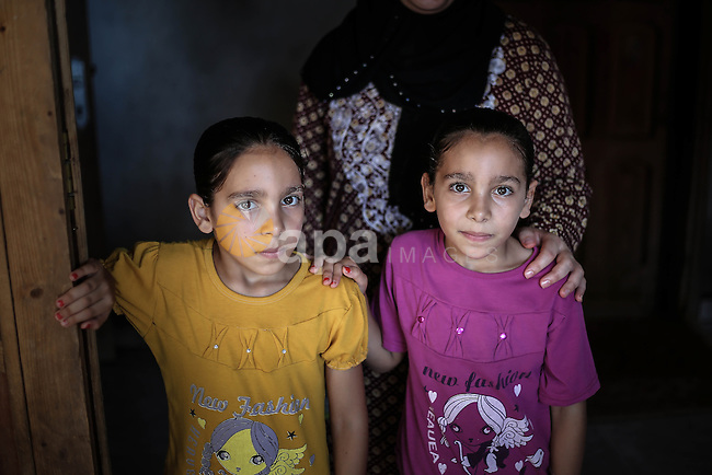 Riham and Hanin Zidan, 8-year-old, a Palestinian twins pose for a photograph at their home at al-Shati refugee camp, western Gaza City, Aug 07, 2013. The mother of Riham and Hanin faced a hard time conceiving a baby for a 15 years of marriage before they are born naturaly. Photo by Mahmoud Hamda