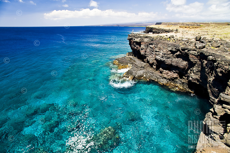 Woman standing at the edge of a cliff overlooking the clear blue water of South Point on the Big Island of Hawaii