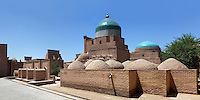 General view of holy tombs and the Pahlavan Makhmoud Mausoleum, Khiva, Uzbekistan, pictured on July 5, 2010, in the morning. The mausoleum centres on the two-cupola shrine of Pahlavan Mahmud, Khiva's  patron saint (said to have been a poet, soldier, furrier, wrestler and healer of diseases), and is also the burial complex of the Qungrat Khans. 19th and 20th century remodelling extended the complex. The Mausoleum's blue dome dominates Khiva's skyline rising above its brick building and domes  of the adjacent graveyard. Khiva, ancient and remote, is the most intact Silk Road city. Ichan Kala, its old town, was the first site in Uzbekistan to become a World Heritage Site(1991). Picture by Manuel Cohen.