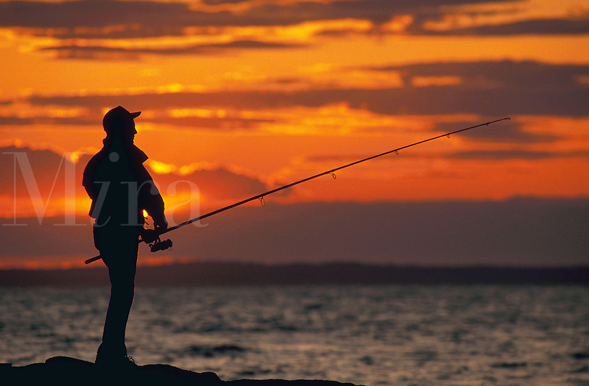 Silhouette of a fisherman at sunset over the ocean.