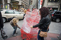 Women attempt to maneuver a cart of baskets through the city streets, seen in Midtown Manhattan New York on Saturday, February 18, 2012. (© Richard B. Levine)