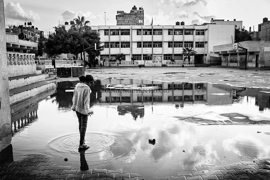 Gaza, Beach Camp : Dalia Alsabagh, 10 ans, marche dans de l'eau de la cour de l'école de l'UNRWA où elle vit après que de fortes pluies soient tombées sur Gaza. 04/11/14<br /> <br /> Gaza, Beach Camp : Dalia Alsabagh, 10 years old, is walking in the water of the courtyard of the UNRWA school where she lives after heavy rains felt on Gaza. 04/11/14