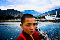 Young Buddhist monks next to the Pho Chhu river next to the Punakha dzong in Punakha, Bhutan.