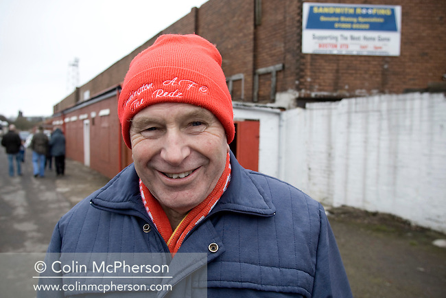 A home supporter smiling prior to the Blue Square North fixture between hosts Workington AFC (red) and Boston United at Borough Park. The visitors won with a solitary sixth-minute goal by Jon Rowan in front of 388 spectators. Both Workington AFC and Boston United were members of the Football League, the Cumbrians losing League status in 1977 while the Lincolnshire club were relegated in 2007 and demoted two divisions for financial irregularities..