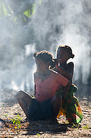 Two young malagasy girls doing each others hair in the smoke of a fire