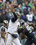 St. Louis Rams quarterback Sam Bradford  passes under pressure from the  Seattle Seahawks Chris Clemons, at CenturyLink Field in Seattle, Washington on December 30, 2012.   Bradford completed 25 of 42 passes for 252 yards, passed for one touchdown and threw one interception in the Rams 13-20 loss to the Seahawks.   © 2102.  Jim Bryant Photo. All Rights Reserved.