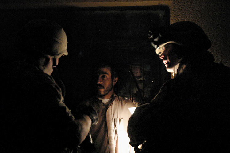 AR RUTBAH, Iraq- A translator (left) and a Marine (right) speak with an Iraqi national in front of his home during a raid performed by Marines from 2D Light Armored Reconnaissance. The Marines of Regimental Combat Team 2 conduct counter-insurgency operations with Iraqi Security Forces to isolate and neutralize anti-Iraqi forces, to support the continued development of Iraqi Security Forces, and to support Iraqi reconstruction and democratic elections in order to create a secure environment that enables Iraqi self-reliance and self-governance. (Official USMC photo by Lance Cpl. Shane S. Keller)