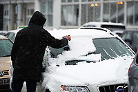 UK Weather: Heavy flurries of snow fall in Aberystwyth, west Wales,  on a cold February morning in Aberystwyth, west Wales, UK. Tuesday 06 February 2018.  A man clears his car windscreen of snow before his journey<br /> The Met Office has issued a &lsquo;yellow&rsquo; warning for snow and ice, as a band of sleet and snow moves in from the west, to cover much of Wales and the north of England