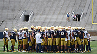 The team huddles on the field at Notre Dame Stadium.
