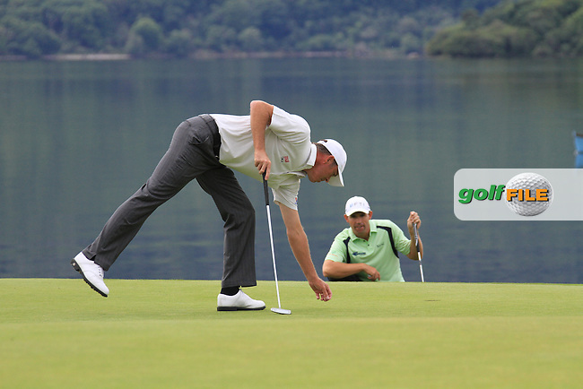 Padraig Harrington lines up his putt as Richard Green repairs pitch mark on the 4th green during the Final Day of the 3 Irish Open at the Killarney Golf & Fishing Club, 1st August 2010..(Picture Eoin Clarke/www.golffile.ie)