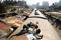 Two boys lie on the roof of a train as it makes its way through Dhaka. Many homeless children live in railway stations and ride trains for fun. However, it is very dangerous and there have been calls for the authorities to prevent children riding on train roofs...