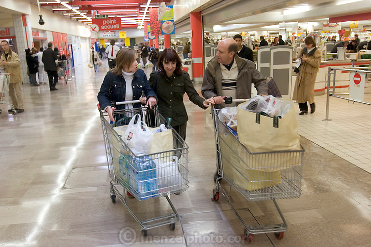 At the end of the Le Moine family's weekly shopping trip to the huge Auchan hypermarket, the family (without Laetitia) pushed their shopping carts to the car park. (Supporting image from the project Hungry Planet: What the World Eats.)