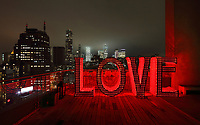 LOVE by Laura Kimpton at night, one of a series of Monumental Word Sculptures, on the roof of the James New York Hotel, Grand St, SoHo, Manhattan, New York, New York, USA. Laura Kimpton's sculptures spread positive messages using large capital letters spelling words which are illuminated at night. Picture by Manuel Cohen