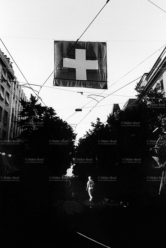 Switzerland. Zürich. Early morning, a man walks on the Bahnhofstrasse which is the main shopping and banking street. He passes under a giant swiss flag. The flag of Switzerland displays a white cross in the centre of a square red field. The white cross is known as the Swiss cross. © 1990 Didier Ruef