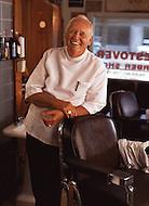 An older man laughs and leans up against a chair in his barber shop.
