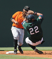 Ronald Bermudez (22) of the Greenville Drive slides with his hands high attempting a steal, but second baseman Juan Martinez (14) of the Augusta GreenJackets already has the ball and makes the tag in a game on May 23, 2010, at Fluor Field at the West End in Greenville, S.C. Photo by: Tom Priddy/Four Seam Images