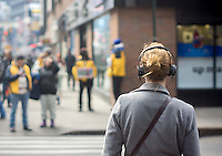 A woman walks down Broadway in Midtown Manhattan in New York wearing her headphones on Sunday, February 2, 2014. (© Richard B. Levine)