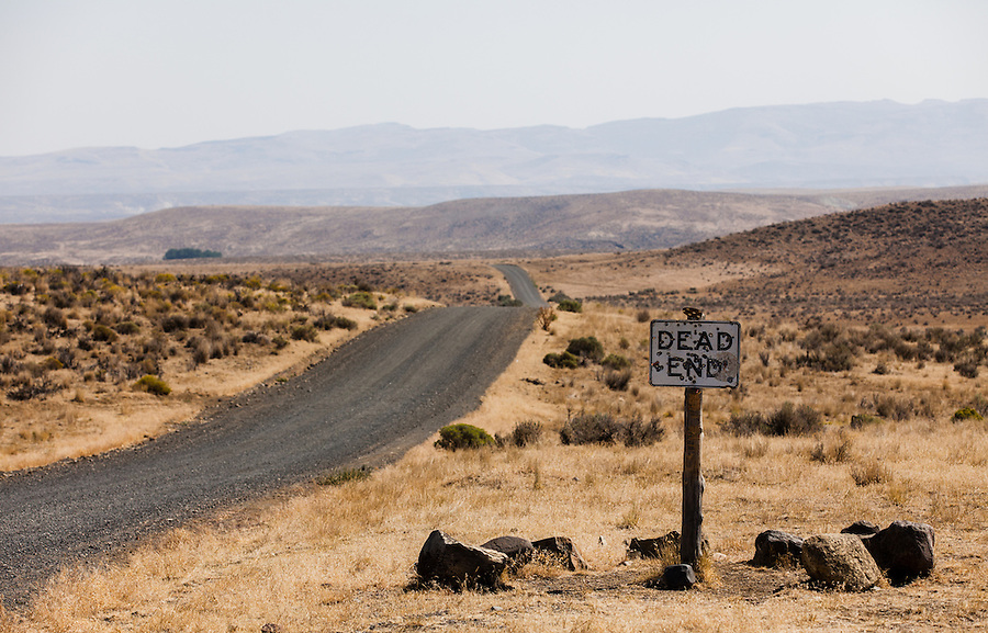 A bullet-ridden dead end sign stands at the entrance to a sagebrush surrounded gravel road that vanished off into the hills in Southeast Oregon.