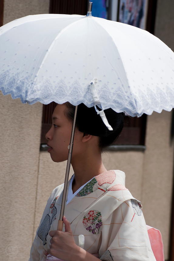The maiko, or apprentice geisha, Takahina, takes a summer stroll down a street in Gion, one of Kyoto's traditional geisha quarters.