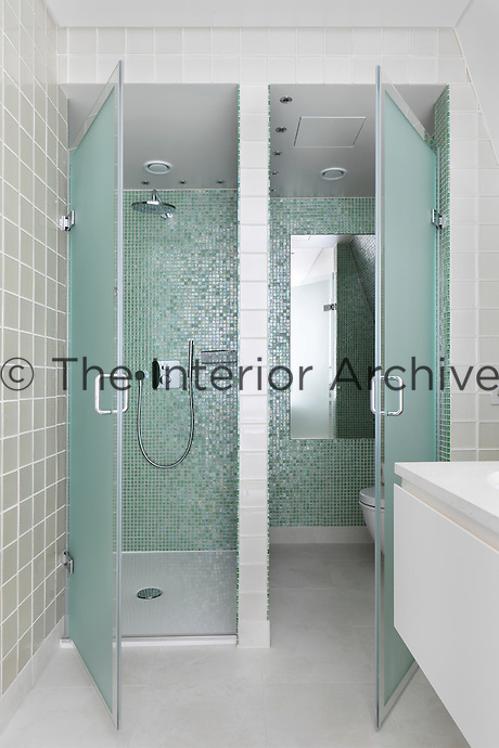 Turquoise mosaic tiles shimmer on the bathroom walls which match the misted glass of the shower and toilet doors