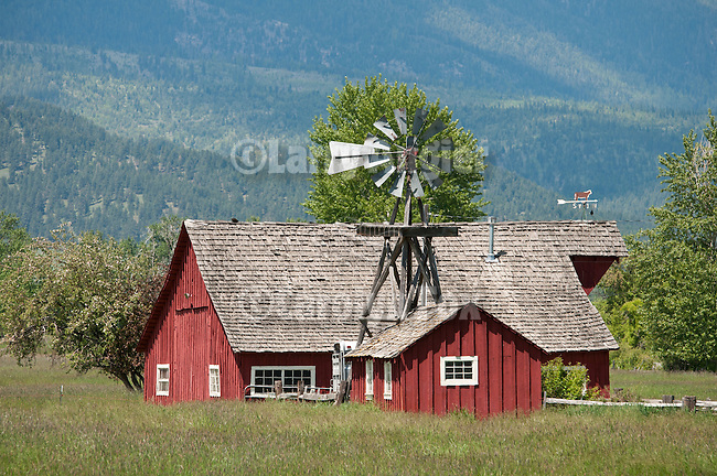 Red barn and shed with metal windmill beneath Oregon's Blue Mountains.