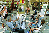 Two artists seated side by side work in broad pedestrian esplanade. Each draws portrait of different young girl. Artists' sample portraits and tearsheets displayed on easels. People, shops and outdoor restaurant in background. Avignon Provence France.