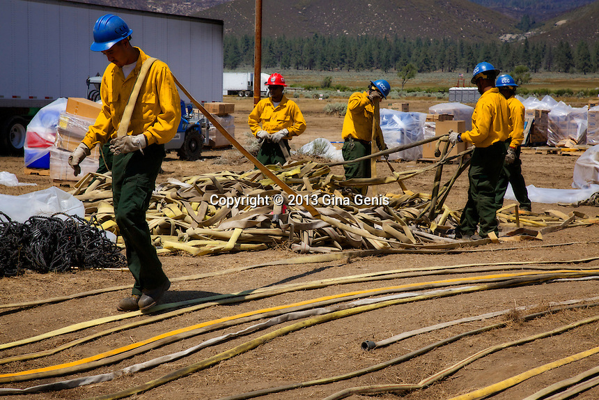 The California Conservation Corps untangles fire hoses used in the Mountain Center fire