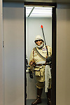 Garden City, New York, U.S. - June 14, 2014 - Wearing a costume of an Ape in khaki miliary uniform, based on the Planet of the Apes movie series, an elevator rider peers out as the door closes, at Eternal Con, the Long Island Comic Con Pop Culture Expo, held at the Cradle of Aviation Museum.