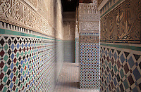 Walls and pillars of the central courtyard of the Al-Attarine Madrasa, a religious school built 1323-25 by the Marinid Sultan Uthman II Abu Said, who ruled 1310-31, in the medina of Fes, Fes-Boulemane, Northern Morocco. This courtyard has a central marble fountain, a zellige tiled floor and lower walls and intricate carved stucco and wooden walls with horseshoe arches and pillars. Cursive Kufic script is included in the tilework and stucco. The medina of Fes was listed as a UNESCO World Heritage Site in 1981. Picture by Manuel Cohen