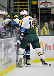 3 December 2011: University of Maine Black Bear defenseman Ryan Hegarty, a Senior from Arlington, MA, is checked into the boards by Matt White of the University of Vermont Catamounts at Gutterson Fieldhouse in Burlington, Vermont. The Catamounts fell to the Black Bears 5-2 in the second game of their 2-game Hockey East weekend series. Mandatory Credit: Ed Wolfstein Photo