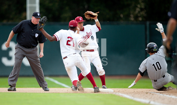 STANFORD, CA - March 27, 2011: Brian Ragira of Stanford baseball forces the batter out at first while Lonnie Kauppila runs to cover the bag during Stanford's game against Long Beach State at Sunken Diamond. Stanford won 6-5.