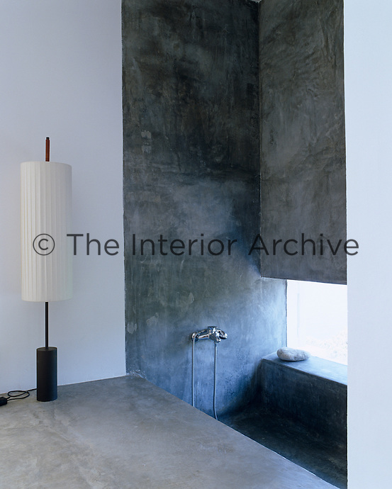 The window in this bathroom is a slit in the concrete wall with a sunken bath beneath it