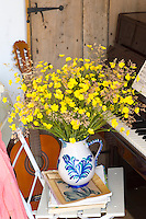 Arranged in a simple blue and white jug a vivid bouquet of buttercups has been placed on a pile of music next to the piano