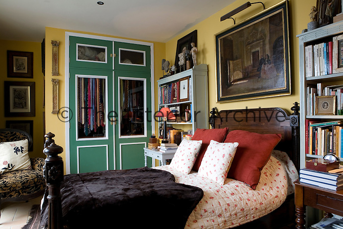 A traditional bedroom decorated in deep yellow and green accent colour. A carved hard wood double bed has a bed cover with terracotta floral pattern and cushions. A Carlos Vasquez painting hangs above the bed.