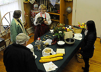 STAFF PHOTO FLIP PUTTHOFF <br /> PEEL MANSION CHRISTMAS<br /> Mary Frizzell, third from left, a volunteer docent at Peel Mansion, shows visitors kitchen items used in the historic home during the Christmas open house at The Peel Mansion and Heritage Gardens in Bentonville. Visitors toured rooms of the historic home that were decorated in various themes while docents in period clothing revealed the mansion's history. The open house was the last opportunity for visitors to see the Peel Mansion decorated for Christmas.