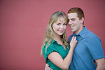 A good-looking, young couple embrace in front of a red wall.