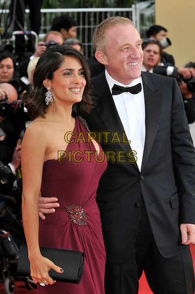 SALMA HAYEK & FRANCOIS PINAULT .wearing Gucci.At the opening ceremony and screening of 'Robin Hood' presented out of competition at the 63rd Cannes Film Festival, Cannes, France, .12th May 2010..arrivals half length burgundy maroon red one shoulder dress slit cut out beaded married husband wife couple black bow tie tuxedo tux side smiling clutch bag .CAP/PL.©Phil Loftus/Capital Pictures.