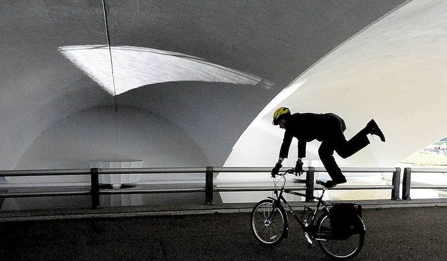 The indefatigueable John Allison, a Pittsburgh Post-Gazette editor and my colleague there, who commutes by bicycle from the north shore daily shows off while wearing business attire during his commute as he passes through the tunnel in Point State Park. The reflecting pool splashes a wedge of light onto the ceiling. <br />