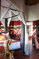 A bedroom at Singita Pamushana Lodge, Malilongwe Trust, Zimbabwe, furnished in colourful red tribal patterns and a four poster bed
